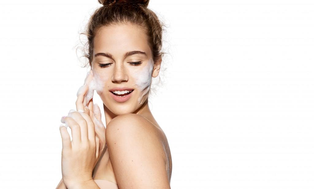 woman using facial wash