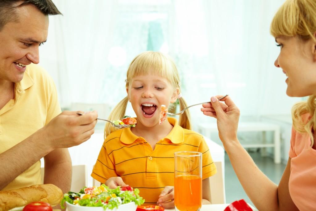 parents feeding their kid