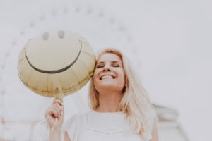 woman smiling holding smiley face balloon