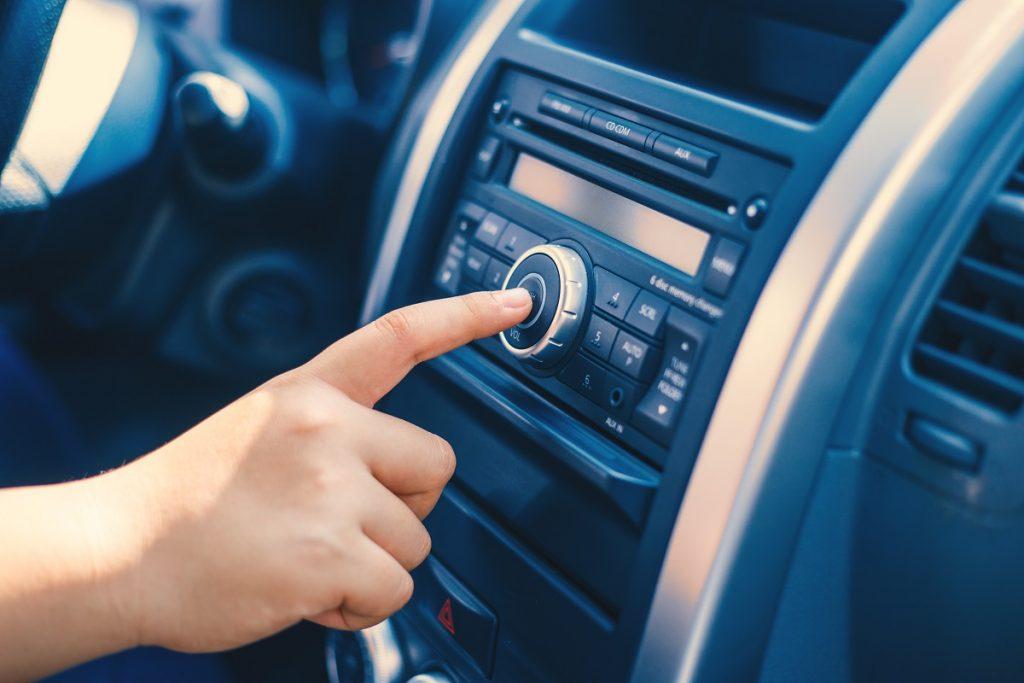 man adjusting dial in car