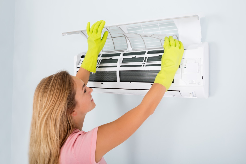 woman fixing an air-conditioning unit